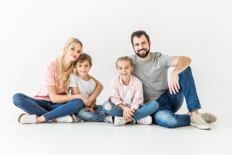 Husband and wife smile while sitting on the floor with their son and daughter in Jonesboro, AR