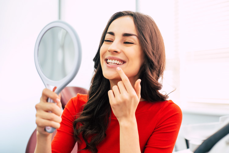 Brunette woman smiles in a handheld mirror after transforming her smile with cosmetic dentistry
