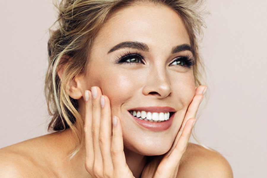 Photo of the facer of a pretty smiling woman with smooth skin