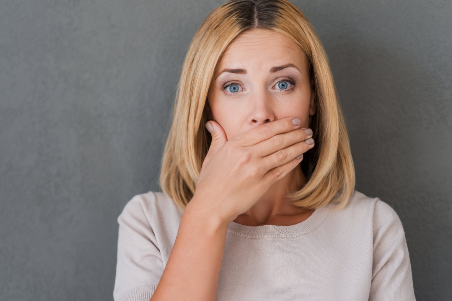 Blonde woman covering her mouth to hide her bad breath.